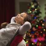 Young woman relaxing on chair in front of Christmas tree